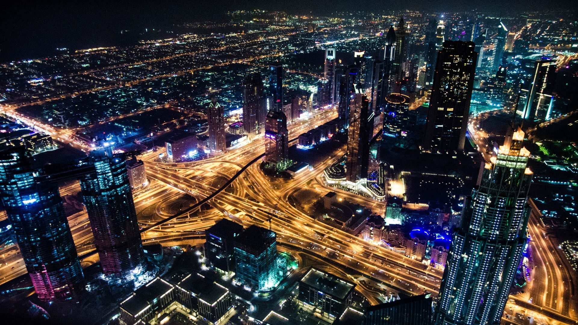 smart, well-lit city at night aerial photograph