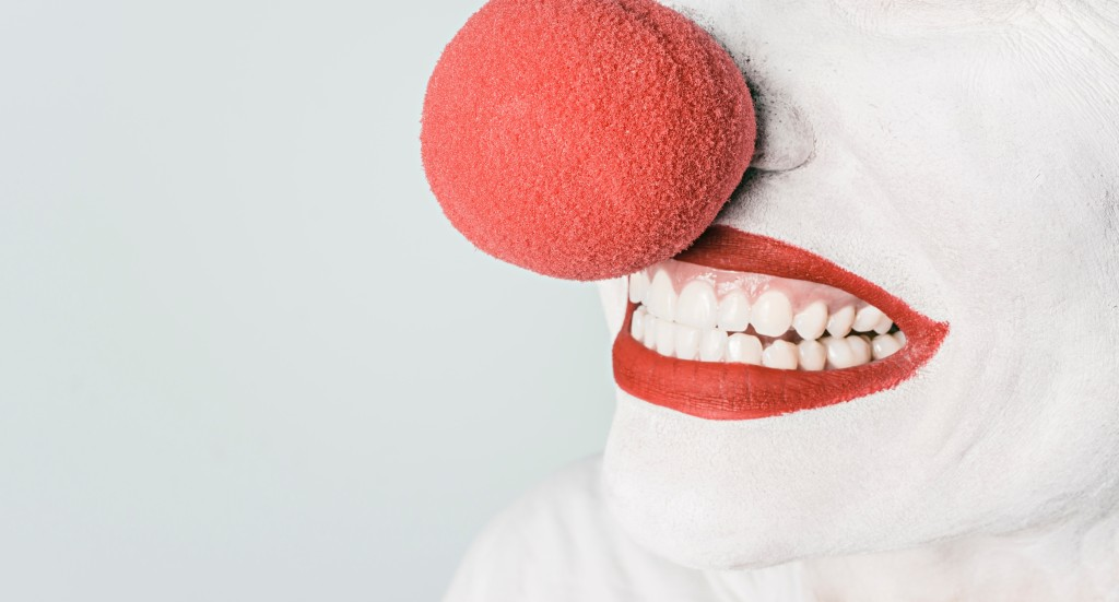 smiling face with white paint, red lipstick, and clown nose