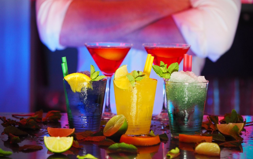 colorful alcoholic drinks fruits man crossed arms